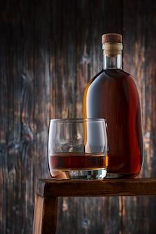 Rundes glas mit einer portion whisky und einer vollen flasche