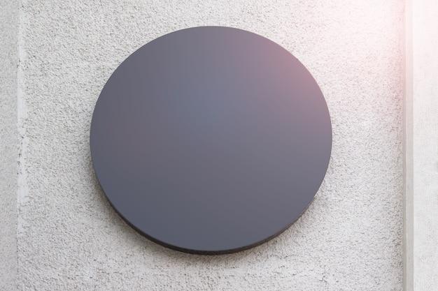 Rundes, graues shop-bannerbrett, das an einer strukturierten wand aus grauem gips hängt