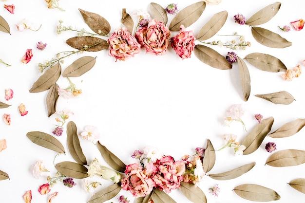 Rundes rahmenkranzmuster mit rosen, rosa blütenknospen, zweigen und getrockneten blättern lokalisiert auf weißer oberfläche