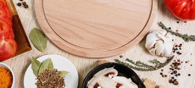 Rundes schneidebrett mit lebensmittelzutaten zum kochen kulinarischer gerichte