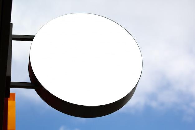 Rundes shopschildmodell gegen blauen himmel