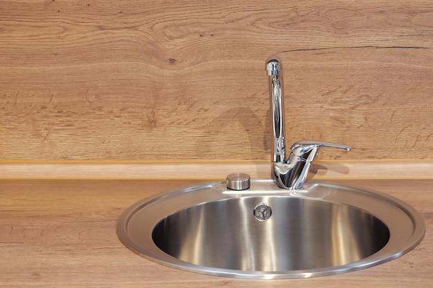 Rundes silberfarbenes waschbecken aus edelstahl mit langem wasserhahn auf der holzküchenoberfläche in der nähe der hellen wand in der nähe