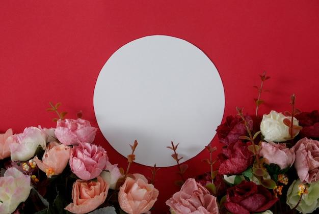 Rundes weißbuch des modells mit platz für text oder bild auf rotem hintergrund und blume.