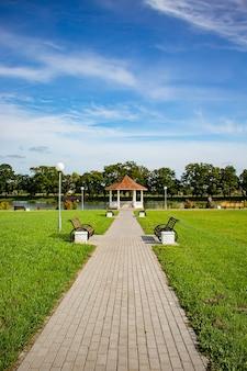 Rundgewölbe in einem park an einem see und ein spazierweg mit bänken