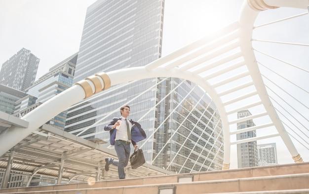 Running business man vor gebäuden beeilen und eilen, weil spät arbeiten