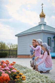 Russisch-orthodoxe frau in einem schal mit ihren töchtern in der nähe der kirche