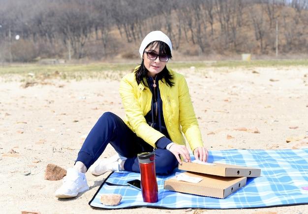 Russische 45-jährige frau wird pizza essen, während sie am strand sitzt