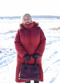 Russische 67-jährige ältere frau im roten mantel, die die kamera gegen schneebedecktes feld betrachtet