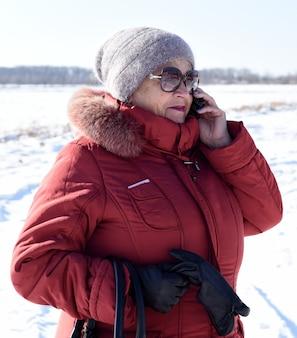 Russische ältere frau, die am telefon gegen schneebedecktes feld spricht