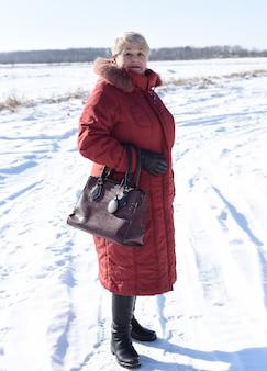 Russische ältere frau, die lächelt und kamera betrachtet
