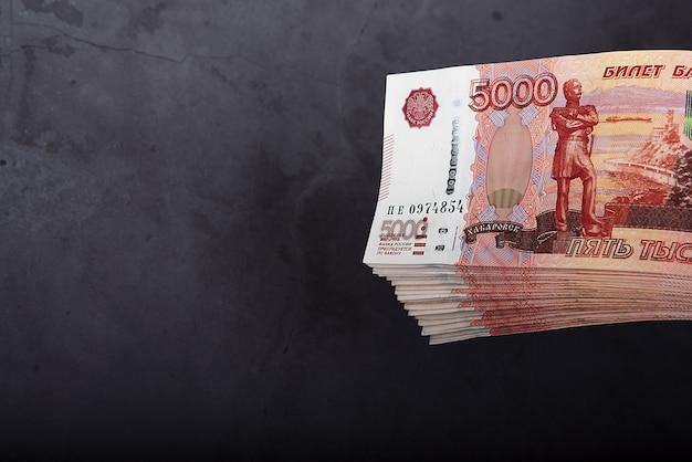 Russische bargeldbanknoten von fünftausend rubel, das bündel hängt auf einem grauen hintergrund
