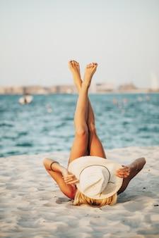 Russische dame im tragen des schwarzen bikinis und des hutes, die auf weißem sand mit beiden füßen oben mit blick auf das blaue wasser des arabischen ozeans liegen und strandtour genießen. bild am besten für lifestyle-magazin-konzept verwendet.