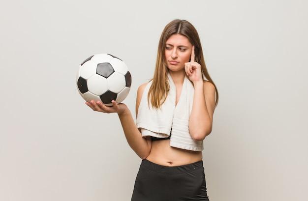 Russische frau der jungen eignung, die eine konzentrationsgeste tut. einen fußball halten.