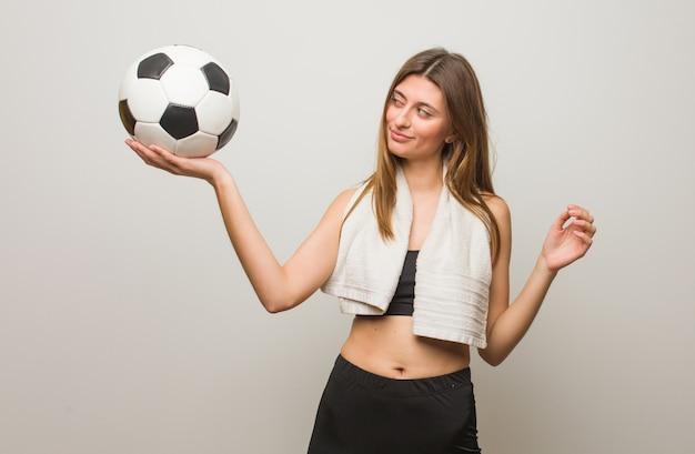 Russische frau der jungen eignung, welche die geste eines fernglases macht. einen fußball halten.