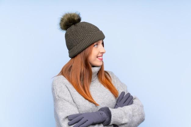 Russische frau der jungen rothaarigen mit winterhut über dem lokalisierten blauen schauen zur seite