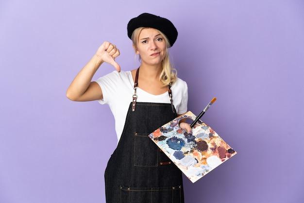 Russische frau des jungen künstlers, die eine palette lokalisiert auf purpurrotem hintergrund hält, der daumen unten mit negativem ausdruck zeigt