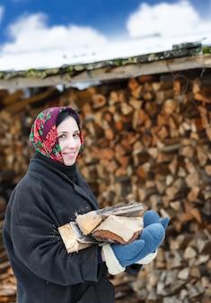 Russische frau in winterkleidung mit brennholz