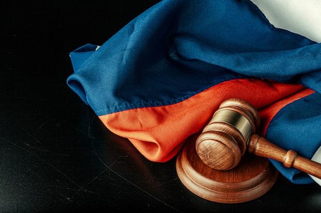 Russische gerechtigkeit. hölzerner hammer und russische flagge