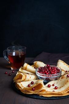 Russische hausgemachte blinis oder pfannkuchen mit beeren in der schüssel serviert auf rundem tablett mit tasse heißen tee