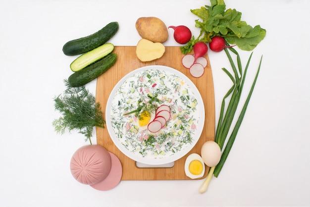 Russische nationale kalte okroschka-suppe in einem weißen teller auf hellem hintergrund. zutaten für hausgemachte okroshka.
