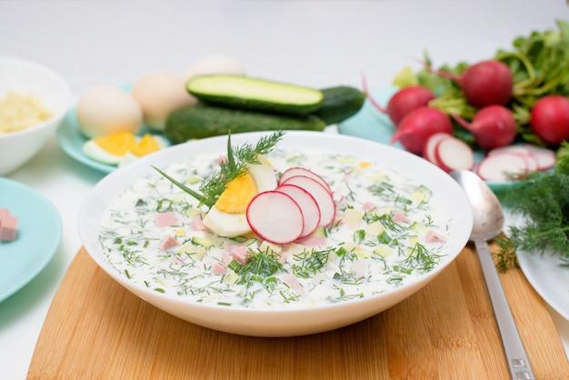 Russische nationale kalte okroschka-suppe in einem weißen teller auf hellem hintergrund.
