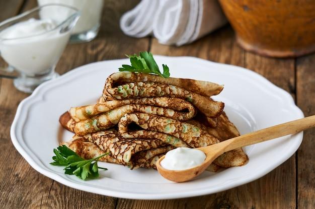 Russische pfannkuchen mit frischer petersilie und sauerrahm auf einer platte