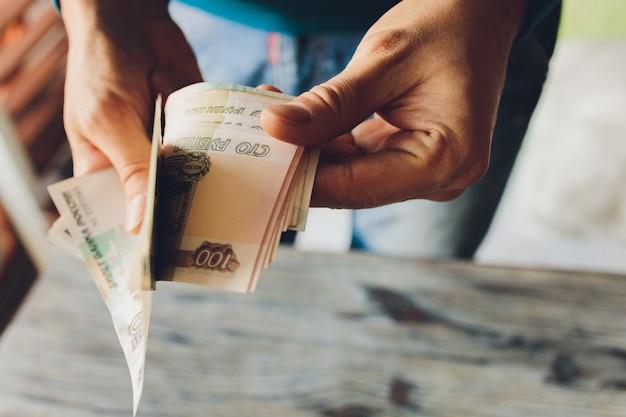 Russische rubel in der hand eines fächers. männliche hand, die viele der russischen banknoten hält. die überweisung von geld. die isolierten fünftausendsten russischen rubel-stückelungen in einer hand.