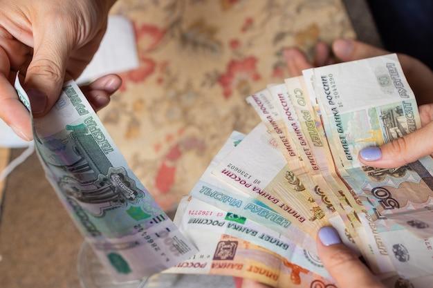 Russische rubel in der hand eines fan.männliche hand, die viele der russischen banknoten hält.der geldtransfer.die isolierten fünftausendstel der russischen rubelbezeichnungen in einer hand.