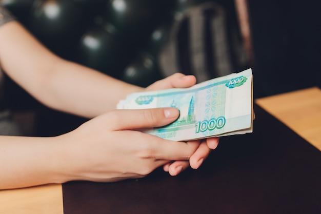 Russische rubel in der hand eines fans. männliche hand hält viele der russischen banknoten. die überweisung von geld.