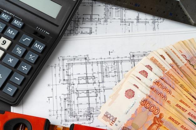 Russische rubel stapeln sich auf blaupausen mit taschenrechner. renovierung, baukostenkonzept