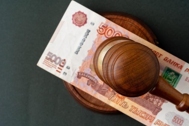 Russische rubelnoten mit richterhammer. korruptionskonzept