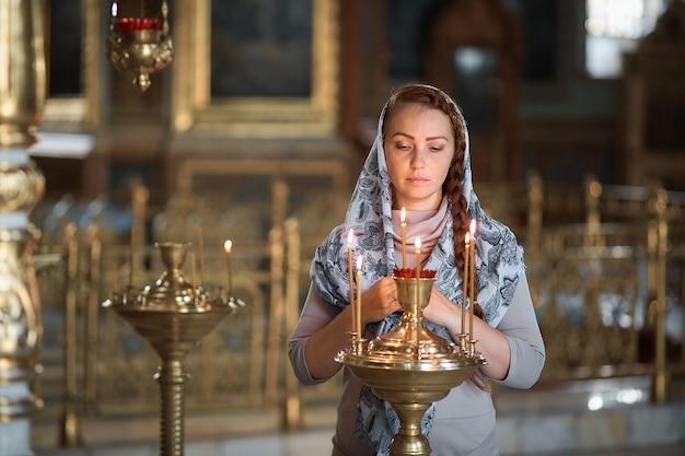 Russische schöne kaukasische frau mit dem roten haar und einem schal auf ihrem kopf ist in der orthodoxen kirche, zündet eine kerze an und betet vor der ikone.
