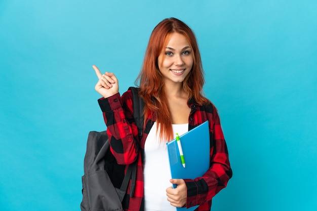 Russische studentin isoliert auf blau glücklich und zeigt nach oben