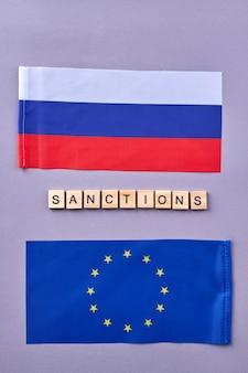 Russische und eu-flaggen. vertikaler schuss des sanktionskonzepts.