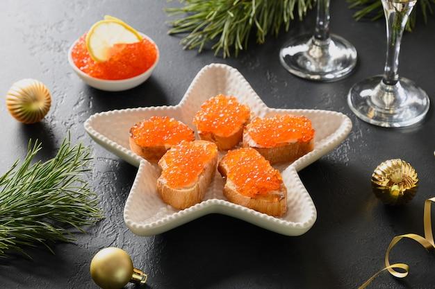 Russischer aperitif-canape mit rotem kaviar auf schwarzem hintergrund zu weihnachten.