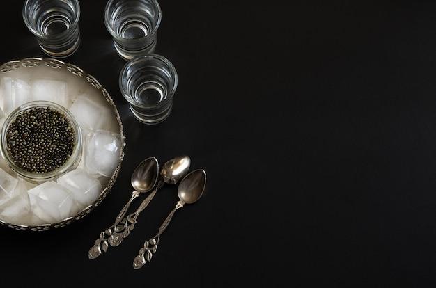Russischer beluga-kaviar, serviert in einer silbernen schüssel mit eis und alkoholischem getränk. schwarzer kaviar delikatessenhintergrund.