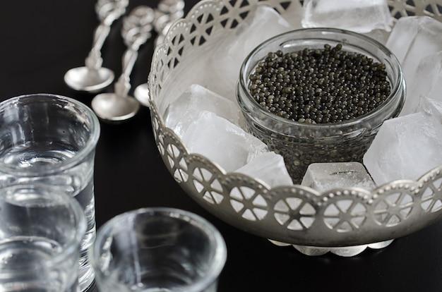 Russischer beluga-kaviar, serviert in einer silbernen schüssel mit eis und alkoholischem getränk
