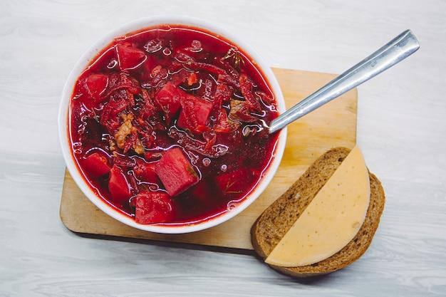 Russischer hausgemachter borschtsch mit brot und käse.