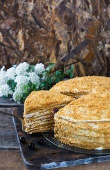 Russischer honeycake medovik auf holztisch und weißem hintergrund. kuchen mit beeren. johannisbeerkuchen