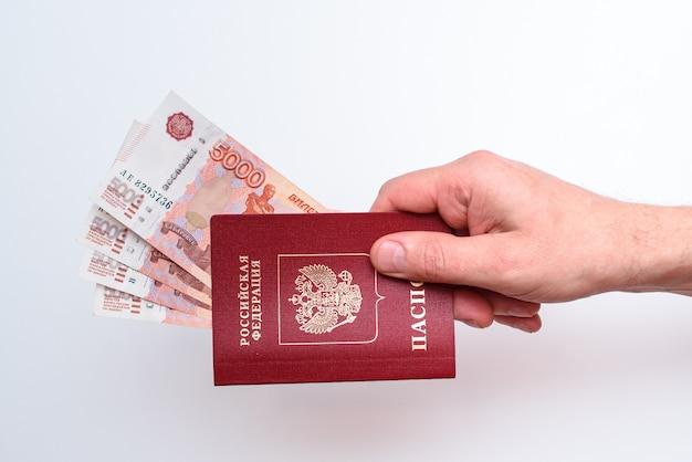 Russischer internationaler pass mit rubeln in der hand des mannes