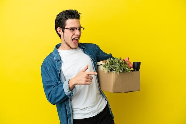 Russischer mann, der eine bewegung macht, während er eine kiste voller dinge aufnimmt, die auf gelbem hintergrund isoliert sind, mit dem finger zur seite zeigen und ein produkt präsentieren present
