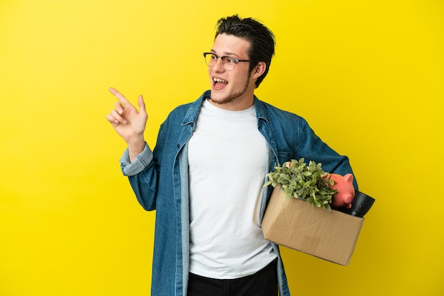 Russischer mann, der eine bewegung macht, während er eine kiste voller dinge aufnimmt, die auf gelbem hintergrund isoliert sind und mit dem finger zur seite zeigen