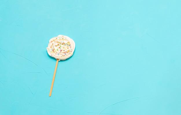 Russischer marshmallow zefir auf einem stock auf hellblauem hintergrund. draufsicht mit kopierraum.