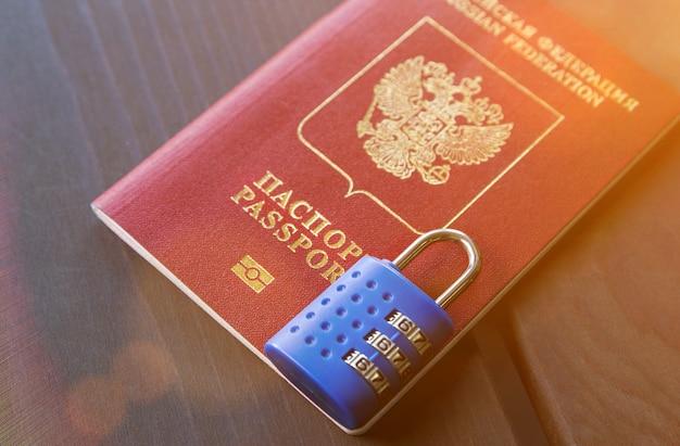 Russischer pass an vorhängeschloss gesperrt. symbol für antirussische sanktionen