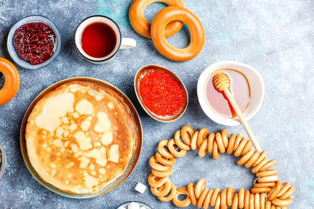 Russischer pfannkuchen-blini mit himbeermarmelade, honig, frischer sahne und rotem kaviar, zuckerwürfeln, hüttenkäse, bubliks auf dunkel