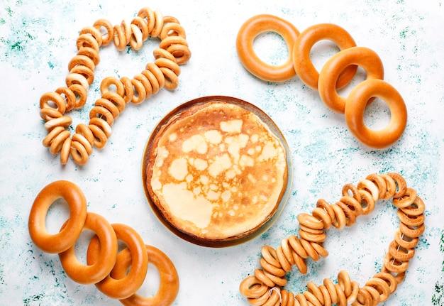 Russischer pfannkuchen-blini mit himbeermarmelade, honig, frischer sahne und rotem kaviar, zuckerwürfeln, hüttenkäse, bubliks