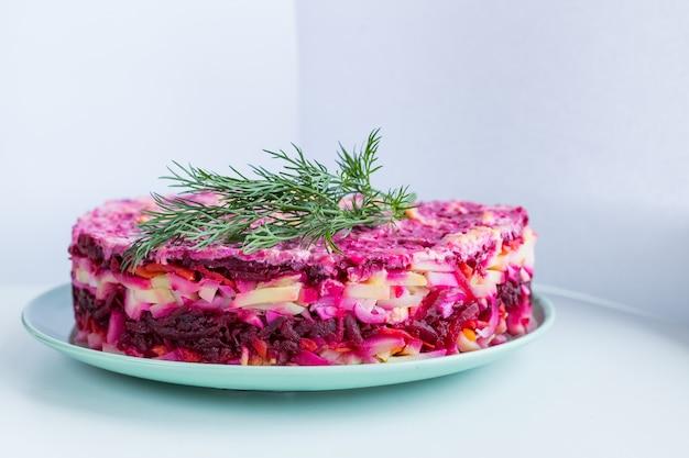 Russischer salat, hering unter pelzmantel. traditioneller heringsalat mit rote beete, karotte, eiern, kartoffeln und rüben auf keramikplatte