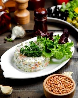 Russischer salat mit kräutern an der spitze