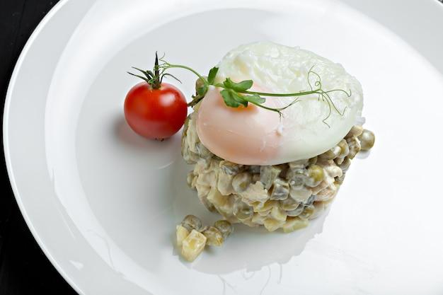 Russischer salat olivier serviert mit pochiertem ei
