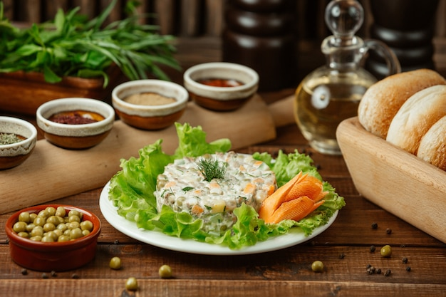 Russischer salat stolichni diente auf blättern des grünen salats und dekorativer karotte mit grünen bohnen